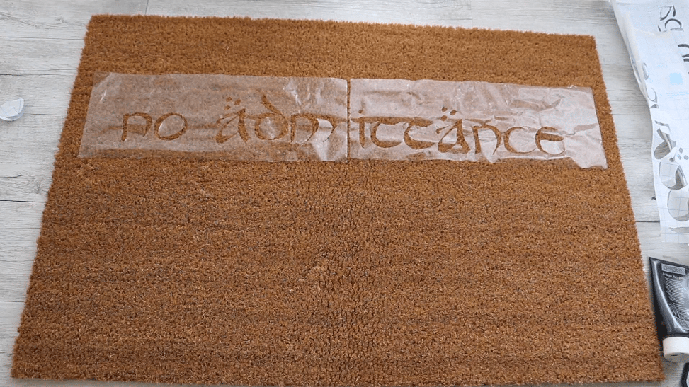 press adhesive contact paper onto mat -- DIY literary doormat project