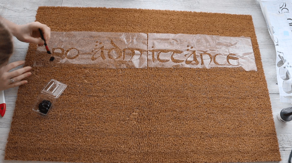 use small eye makeup brush to dab paint on--DIY literary doormat project